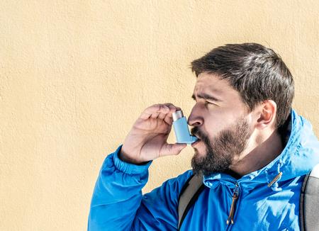 Portret van een jonge man met behulp van astma-inhalator buiten