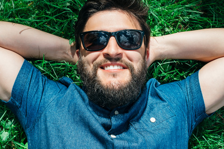 Smiling young man lying, dreaming and relaxing on green grass Stock Photo