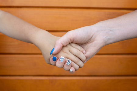 Mother and son holding hand in hand against brown wooden background