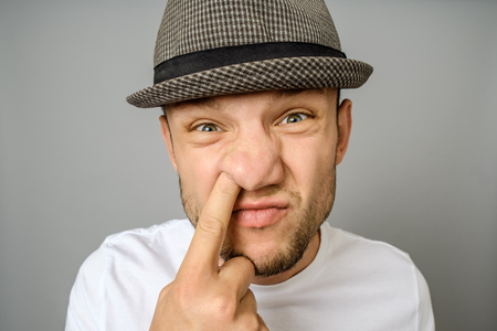 Man picking his nose. The emotional portrait of man in hat and blank t-shirt. Gray background 스톡 콘텐츠