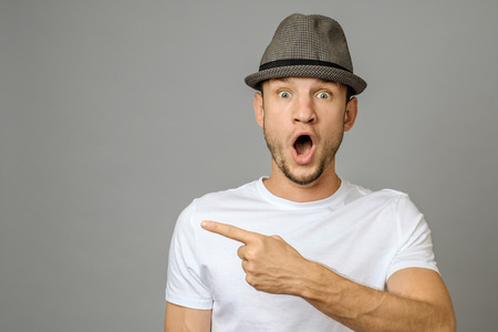 Surprised young man with beard pointing copy space