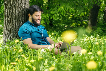 Young businessman or student in casual dress using laptop in the park. Outdoor office concept