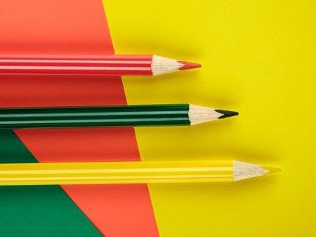 Colored pencils green, yellow and red on color papers geometry flat composition background
