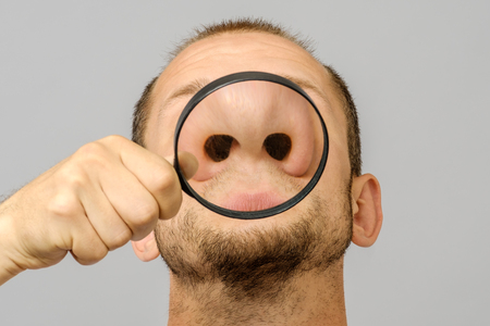 Portrait of caucasian man with magnifier makes fun face. Magnifier to the nose Stock Photo