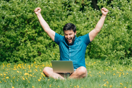 Smiling young man sitting on green grass with raised his hands up and with laptop on his crossed legs