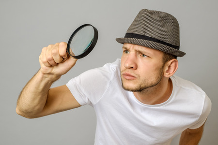 Astonished man looking through a magnifying glass on gray background Stock Photo