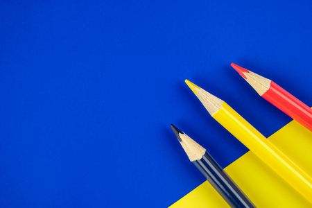 Colored pencils blue, yellow and red on color papers geometry flat composition background
