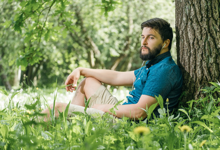 Young man listening to music in green summer forest and relaxing