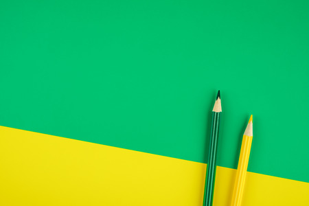 Green and yellow colored pencils on colored paper background. Minimalist creative concept