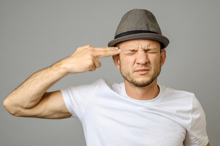 Young man makes suicide gesture and going to kill himself. Unhappy man in panic shooting with fingers Stock Photo