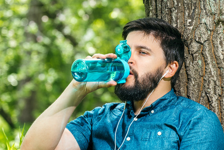 Close up portrait of a man drinking water from a bottle outside. Young man drinking water in the forest