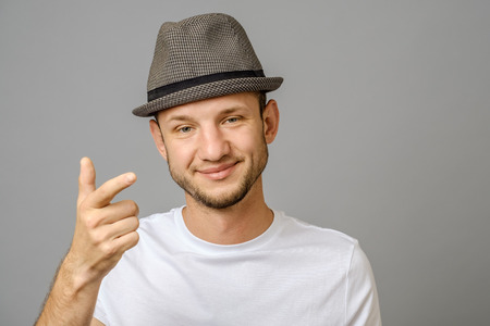 Young man showing his index finger towards the camera