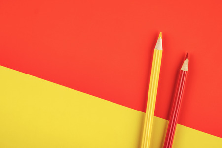 Colored pencils yellow and red on color papers geometry flat composition background