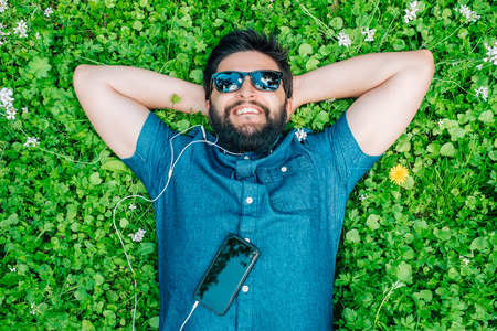Carefree man with sunglasses lying on the grass and listening music in springtime