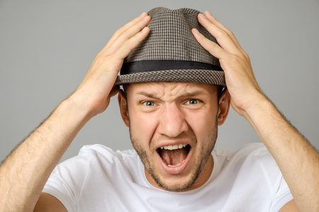 Portrait of angry screaming young man on gray background