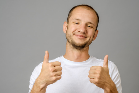 Portrait of man smiling and showing two thumbs up on gray background Stock Photo