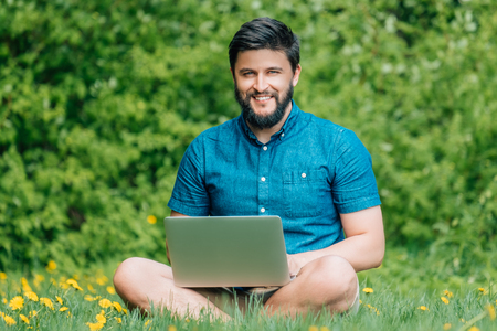 Young modern businessman freelancer working on computer and sitting on grass. Male student using notebook outdoors. Tourist working on laptop