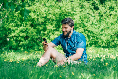 Young man sitting in the park and texting message. Smiling man on the grass using smartphone Stock Photo