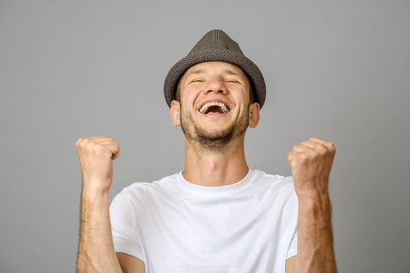 Happy young man with his arms up in victory gesture on gray background Фото со стока