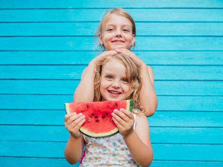 Dos hermanitas junto con sandía madura roja sonriendo. Sobre fondo de pared de tablón azul Foto de archivo