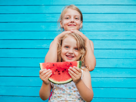 Two little sisters together with red ripe watermelon smiling. Over blue plank wall background Foto de archivo