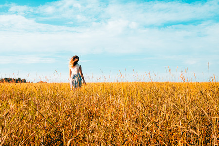 Portrait of a beautiful young woman in a dress walking through the wheat field 版權商用圖片