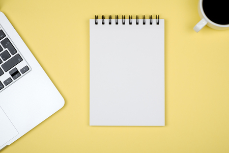 Minimal workplace with laptop and blank notepad on colored background. Top view. Flat lay