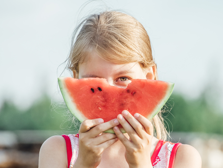 Portrait of blonde little girl with watermelon. Child at summer outdoors with ripe red  watermelon
