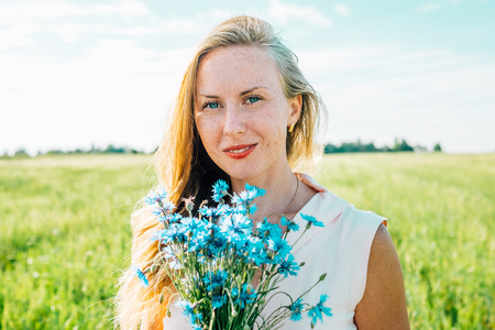 Young freckled woman with bouquet of cornflowers in a meadow