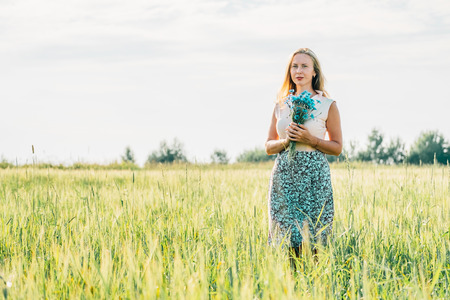 Young freckled woman with bouquet of cornflowers in a meadow Foto de archivo - 117435906