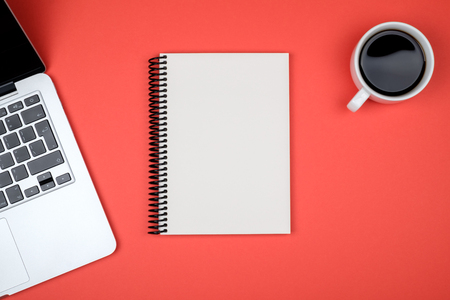 Modern designer office desk table with blank notebook page, laptop computer and cup of coffee. Top view, flat lay Stock Photo