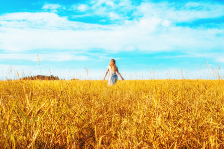 Young woman on a wheat field with sunlight Foto de archivo - 117430108