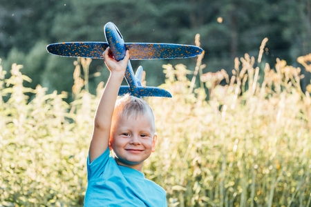 Happy child dreams of traveling and playing with an airplane. Aviator in outdoor in the summer Stock Photo