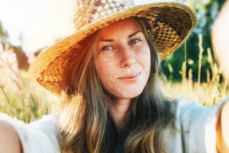 Self portrait of beautiful young blonde smiling woman in straw hat on nature background in the park. Travel. Selfie Foto de archivo - 117430112