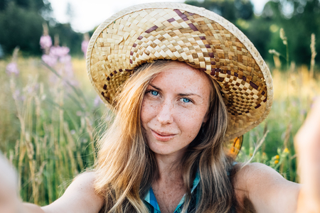 Self portrait of beautiful young blonde smiling woman in straw hat on nature background in the park. Travel. Selfie