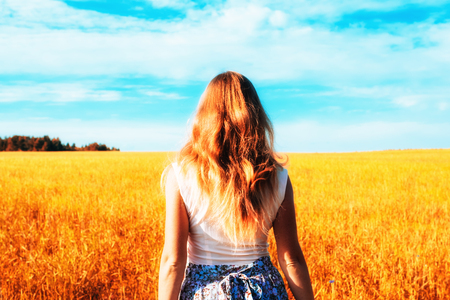 Young woman in dress walking along cereal field. Concept of happiness, loneliness, summer, countryside vacation Foto de archivo - 117433888