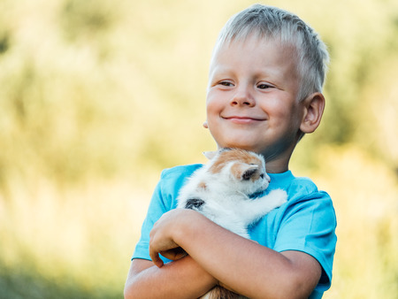 Little boy at countryside holding his lovely fluffy kitty cat. Pets and lifestyle concept Foto de archivo - 117433894