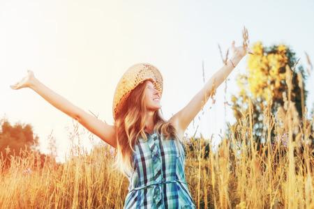 Young woman enjoying summer evening outdoors. The sun is shining Foto de archivo - 117433900