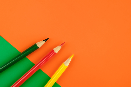 Red, green and yellow colored pencils on colored paper background. Minimalist creative concept