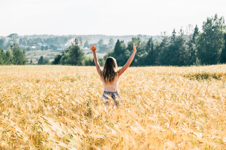 Young woman in dress walking along cereal field. Concept of happiness, loneliness, summer, countryside vacation Foto de archivo - 117435791