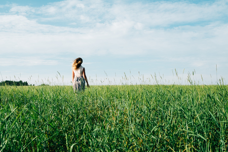 Young woman in dress walking along cereal field. Concept of happiness, loneliness, summer, countryside vacation Foto de archivo - 117435799