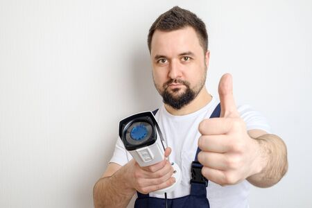 Technician or contractor with CCTV security camera showing thumbs up gesture
