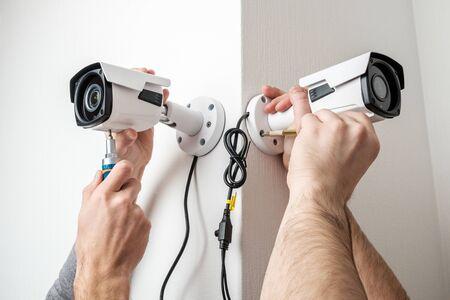Close-up handen van technicus die kabeltelevisie-camera op muur aanpast