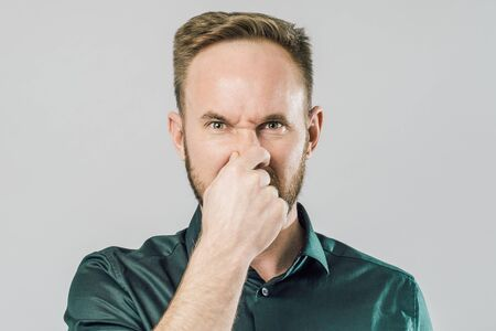 Portrait of disgusted funny guy, covering nose with fingers and frowning from displeasure over gray background