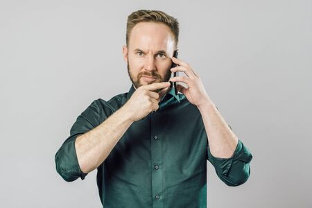 Man with index finger pointing to smartphone, ask to be quiet. Important call concept. Isolated on gray Stock Photo