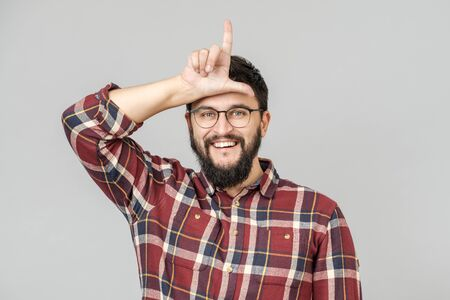 Portrait of happy guy with showing loser sign over forehead and smiling, bragging about victory, over gray background