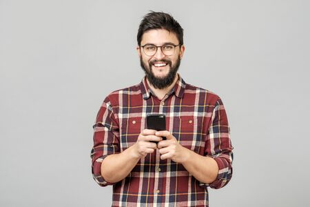 Portrait of handsome european man holding telephone while texting, isolated over gray background. Laughing at meme his friend sent, answering with funny emoji