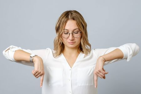 Portrait of young woman dressed in white pointing fingers down at copy space isolated over gray background Фото со стока