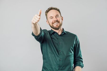 Portrait of friendly and excited supportive man in green shirt, raising thumbs up and smiling broadly while liking idea or cheering, accepting great plan. Isolated over gray