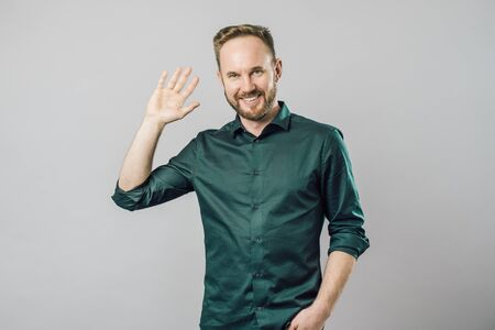 Shot of friendly and happy young bearded man in green shirt waving raised hand in hello gesture smiling at camera. Greeting saying hi over gray background